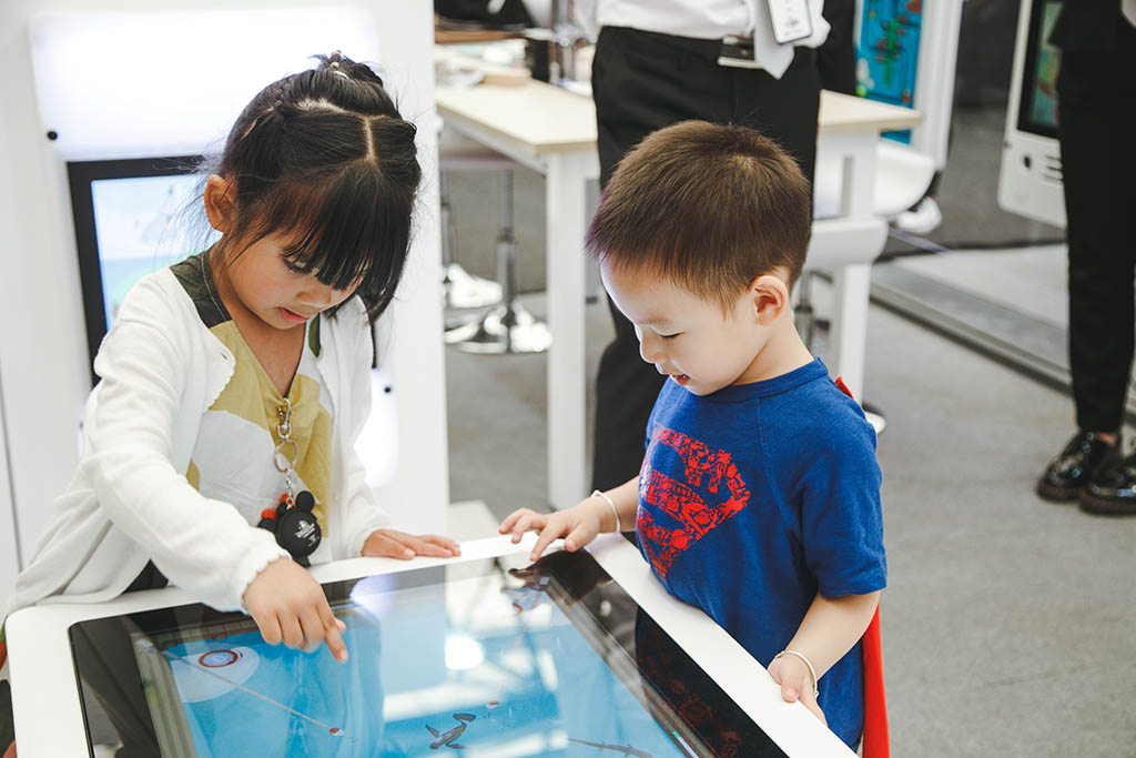 this image shows 2 kids with in interactive play table